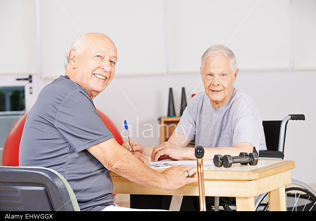 EHWGGX Two old men sitting in a nursing home and solving a crossword puzzle