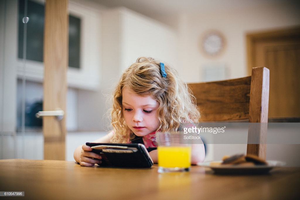 Little girl watching streamed tv on her mothers smartphone while sat at the dining table eating snacks.